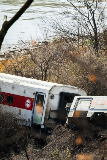 A Metro-North commuter train lies in the brush near the Hudson River after it derailed just north of the Spuyten Duyvil station December 1, 2013 in the Bronx borough of New York City. Multiple injuries and at least 4 deaths were reported after the seven car train left the tracks as it was heading to Grand Central Terminal along the Hudson River line. (Christopher Gregory/Getty Images)