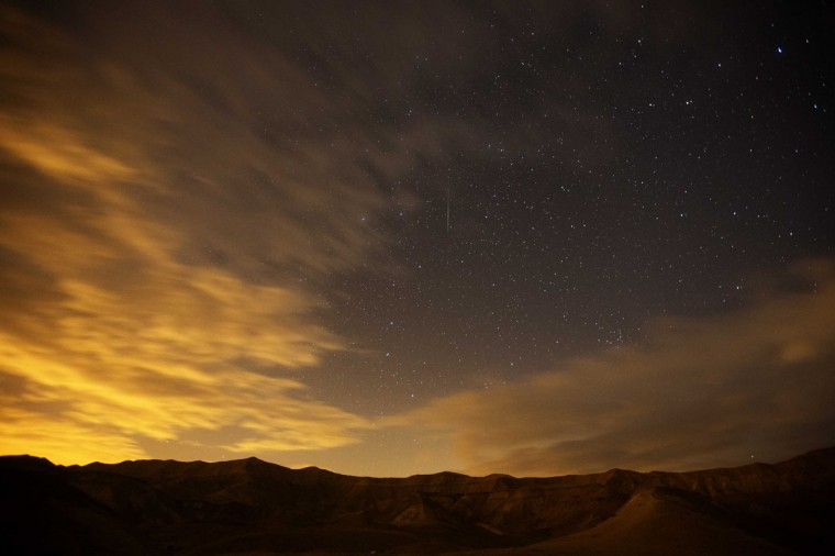 A Geminid meteor streaks are seen above the Judean desert near near the Israeli Kibbutz of Ein Gedi early December 14, 2012. The meteor display, known as the Geminid meteor shower because it appears to radiate from the constellation Gemini, is thought to be the result of debris cast off from an asteroid-like object called 3200 Phaethon. The shower is visible every December. (Menahem Kahan/AFP/Getty Images)