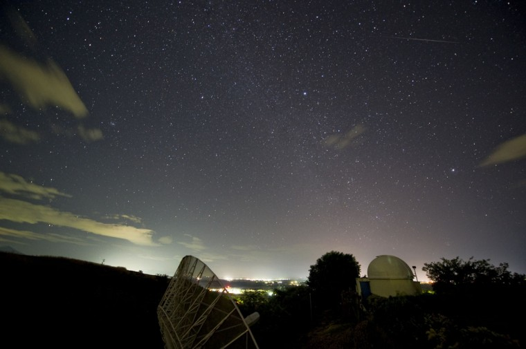 """A meteor (right) from the Geminids meteor shower enters the Earth's atmosphere, seen from the Prudencio Llach observatory in San Juan Talpa, 40 kms south of San Salvador on December 13, 2012. The US space agency NASA said on December 10 that the best meteor shower of the year, a display of shooting stars known as the Geminids, began on December 7 and was set to peak early on December 11, lasting for several days. The annual Geminids meteor shower was first glimpsed late in the 19th century, but at that time """"the shower was weak and attracted little attention"""". (Jose Cabezas/AFP/Getty Images)"""