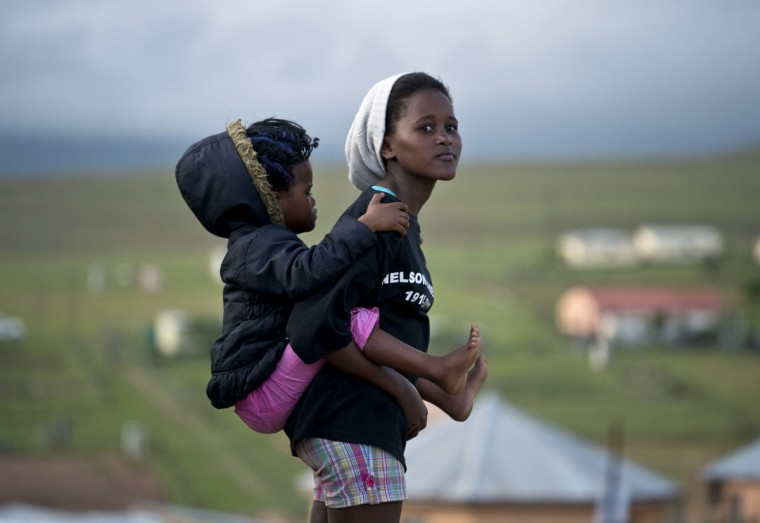 A young woman carrying a baby looks towards Nelson Mandela's family house in Qunu where the coffin of South African former president arrived on December 14, 2013 before his funeral tomorrow. Mandela, the revered icon of the anti-apartheid struggle in South Africa and one of the towering political figures of the 20th century, died in Johannesburg on December 5 at age 95. (Pedro Ugarte/AFP Photo)