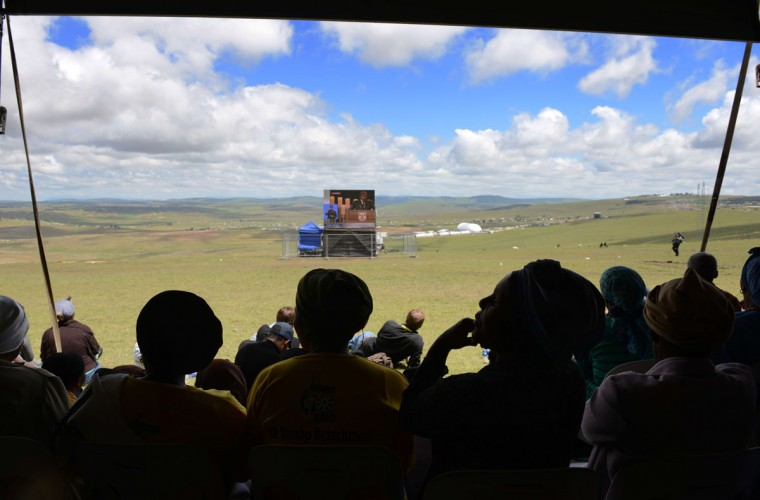 A local woman joins others under a tent as they watch the funeral on a giant screen in a hill overlooking the valley where South African President Nelson Mandela will be laid to rest on December 15, 2013 in Qunu. South Africa's first black president Nelson Mandela received a tearful state funeral at his childhood village of Qunu on Sunday, followed by a traditional burial attended by family and friends. Mandela, the revered icon of the anti-apartheid struggle in South Africa and one of the towering political figures of the 20th century, died in Johannesburg on December 5 at age 95. (Roberto Schmidt/AFP/Getty Images)