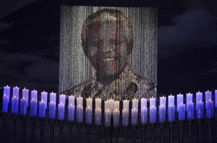 Candles are lit under a portrait of former South African President Nelson Mandela before his funeral ceremony in Qunu December 15, 2013. (Odd Andersen/Reuters)