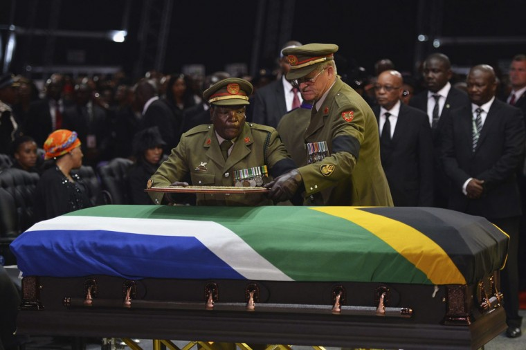 Members of the military leave a frame on the coffin of former South African President Nelson Mandela during his funeral ceremony in Qunu December 15, 2013. (Odd Andersen/Reuters)