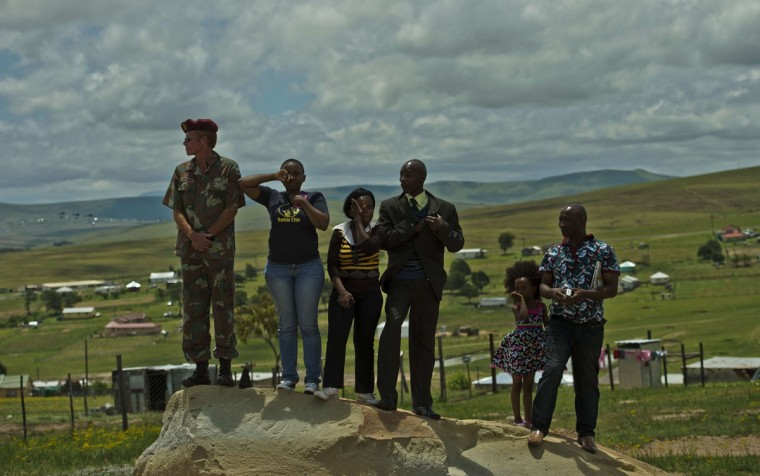 People react as the coffin of South African leader Nelson Mandela is buried in the compound of his former home in Qunu on December 15 2013. Mandela, the revered icon of the anti-apartheid struggle in South Africa and one of the towering political figures of the 20th century, died in Johannesburg on December 5 at age 95. (Carl De Souza/AFP/Getty Images)