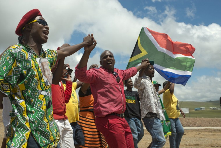 People sing nearby the funeral place of South African former president Nelson Mandela in Qunu on December 15, 2013. Mandela, the revered icon of the anti-apartheid struggle in South Africa and one of the towering political figures of the 20th century, died in Johannesburg on December 5 at age 95. (Roberto Schmidt/AFP/Getty Images)