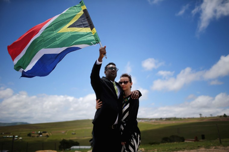 Karlind Govender and his wife Katharina, of Cape Town overlook the burial site as a 21 gun salute is fired in honour of former South African President Nelson Mandela during his state funeral December 15, 2013 in Qunu, South Africa. (Christopher Furlong/Getty Images)