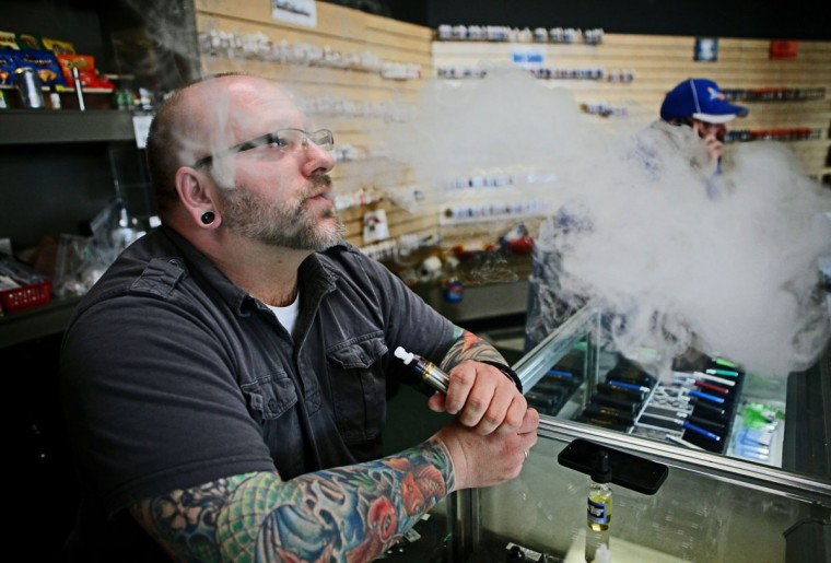 Matt Kostecki, of Milwaukee, who helps out at the store Milwaukee Vapor, exhales some of the vaporized e-juice from the e-cigarette, Dec. 6, 2013, in Milwaukee. (Michael Sears/Milwaukee Journal Sentinel/MCT)
