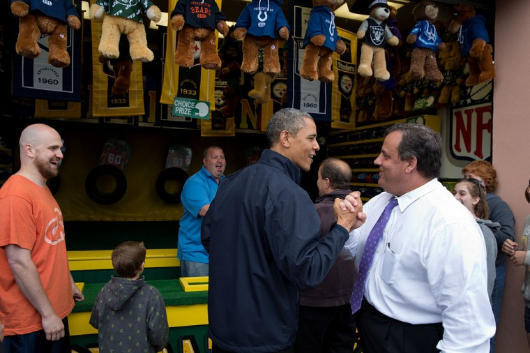 "May 28, 2013 ""The President congratulates New Jersey Gov. Chris Christie while playing the ""TouchDown Fever"" arcade game along the Point Pleasant boardwalk in Point Pleasant Beach, N.J. The President toured the boardwalk which had reopened following the devastation of Hurricane Sandy in 2012."" (Official White House Photo by Pete Souza)"