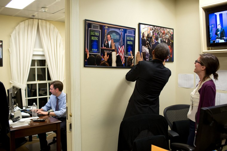 "April 19, 2013 ""The President was about to make a statement in the White House Briefing Room and noticed the photographs hanging on the wall in the Press Office were crooked. So he took matters into his own hands, straightening the pictures as Press Assistant Marie Aberger watched. Deputy Press Secretary works in his office in the background."" (Official White House Photo by Pete Souza)"