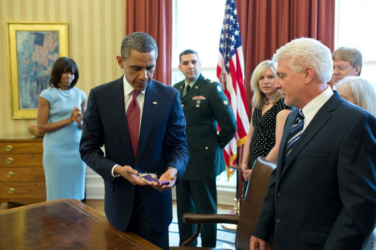 "April 11, 2013 ""The President holds Chaplain (Captain) Emil Kapaun's Easter stole during a greet with Father Kapaun's family in the Oval Office, before posthumously awarding him the Medal of Honor. After being captured by the Chinese military in 1950, Father Kapaun was taken to a North Korean prison camp, where he later died but not before he held an Easter service and said prayers for his captors."" (Official White House Photo by Pete Souza)"