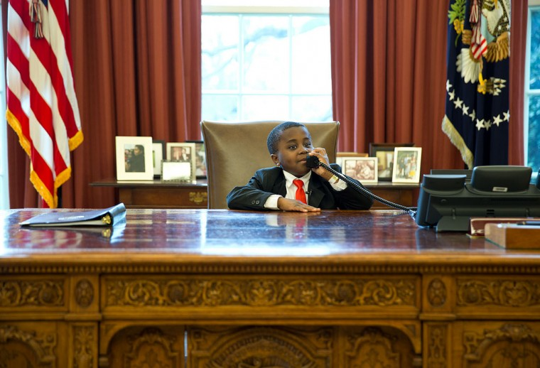 "April 1, 2013 ""Robby Novak, AKA 'Kid President', feigns a phone call at the Resolute Desk during his visit to see the President in the Oval Office. 'Kid President' became a YouTube sensation and was invited to participate in the Easter Egg Roll at the White House."" (Official White House Photo by Pete Souza)"