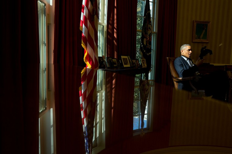 "March 15, 2013 ""A glass-top table serves as a reflection as the President President talks with staff in the Oval Office."" (Official White House Photo by Pete Souza)"