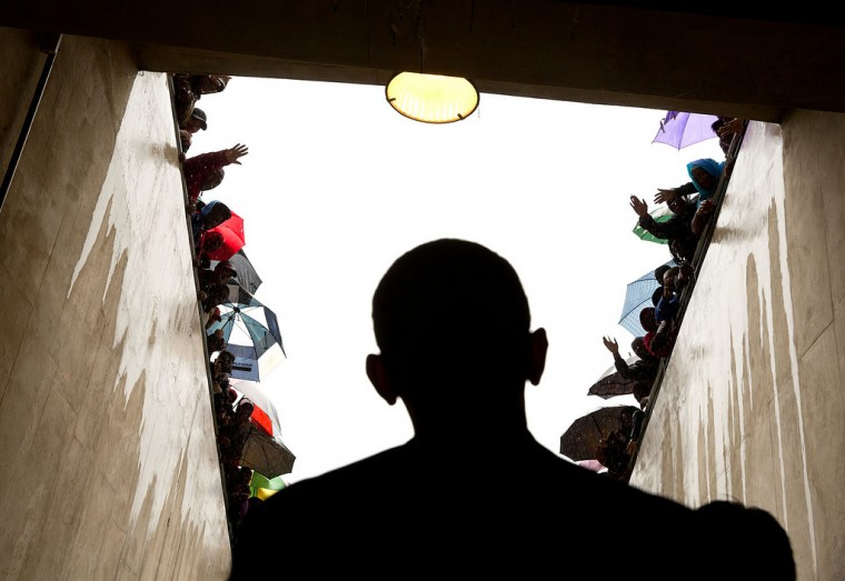 "Dec. 10, 2012 ""South Africans cheer as President Obama waits in a tunnel at the soccer stadium before taking the stage to speak at Nelson Mandela's memorial service. It was a long overnight flight to Johannesburg, a few hours on the ground in the pouring rain, and then a long flight back to Washington."" (Official White House Photo by Pete Souza)"
