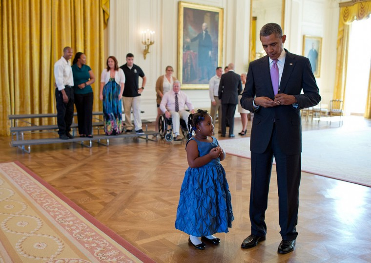 "Sept. 19, 2013 ""I loved the look Alanah Poullard's face as the President wrote a school excuse note for the five-year-old, while visiting with Wounded Warriors and their families in the East Room during their tour of the White House. Alanah asked for a note to show her kindergarten teacher so she wouldn't get in trouble for missing a school day."" (Official White House Photo by Pete Souza)"