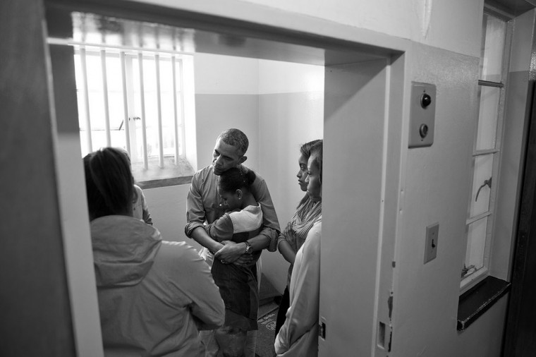 "June 30, 2013 ""A quiet moment inside Nelson Mandela's former prison cell as the President embraced Sasha while the Obama family was listening to Ahmed Kathrada recount his years spent imprisoned here on Robben Island in Cape Town, South Africa. Nelson Mandela was imprisoned for 27 years, initially in this prison cell. Kathrada was imprisoned at Robben Island for 18 years."" (Official White House Photo by Pete Souza)"