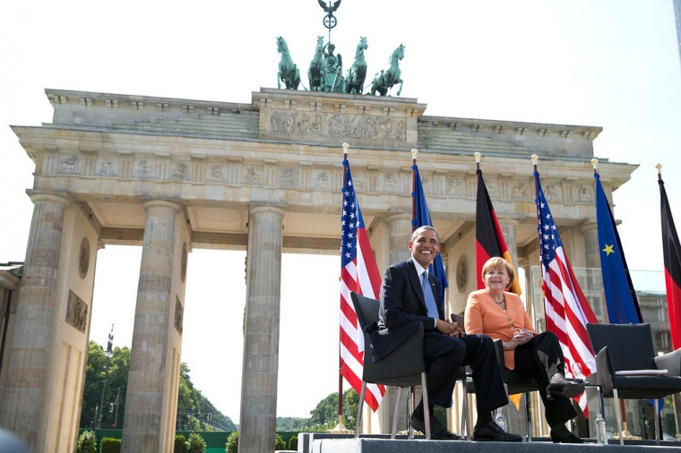"June 19, 2013 ""The President and German Chancellor Angela Merkel listen to remarks by Berlin Mayor Klaus Wowereit at the Brandenburg Gate in Berlin. The last time I had been here was in 1987 on the opposite site of the Gate when President Reagan had challenged Russian President Mikhail Gorbachev to 'tear down this wall.'"" (Official White House Photo by Pete Souza)"