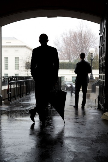 "March 12, 2013 ""The President leans on an umbrella as he waited for heavy rain to let up before crossing from the Eisenhower Executive Office Building to the West Wing of the White House. Most of the staff and Secret Service with the President didn't have umbrellas so he waited for the rain to subside before crossing. I was behind the President, hoping that someone with an umbrella would walk by in the background to add another element to the photograph."" (Official White House Photo by Pete Souza)"