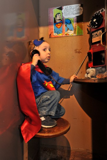 "Lucas Taylor, 2, of Columbia listens to a message for Batman in a vintage phone booth at ""Zap! Pow! Bam! The Superhero, 1938 - 1950,"" an exhibit which opened January 27, 2013 at The Jewish Museum of Maryland. (Amy Davis / Baltimore Sun)"