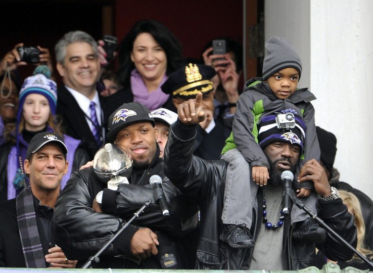 Ravens player Terrell Suggs, left, hugs the Lombardi Trophy as teammate Ed Reed, right, speaks to the crowd at the Ravens Superbowl parade, which started at City Hall on February 5, 2013. (Barbara Haddock Taylor/Baltimore Sun)