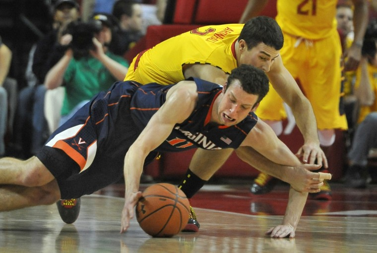 University of Maryland's Logan Aronhalt, in yellow, chases Virginia's Evan Nolte for a loose ball as the Terps fall to the Cavaliers in College Park on February 10, 2013. (Amy Davis/Baltimore Sun)