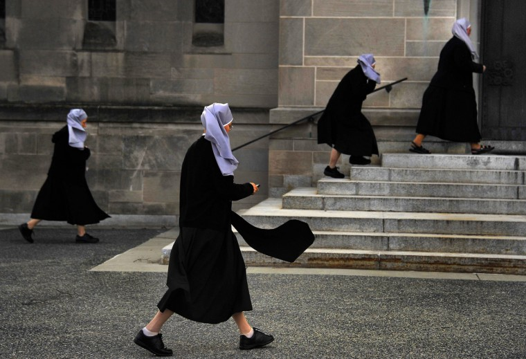 One nun checks her cell phone as other nuns head for the cathedral for Mass at Cathedral of Mary Our Queen, shortly after the installation of Pope Francis on March 13, 2013. (Karl Merton Ferron/Baltimore Sun)