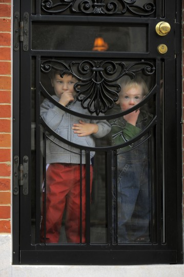 Mark Parker's son, Luke Parker, 2-1/2 (left) peers through the storm door with cousin Ben Myers, 1-1/2 at Parker's Highlandtown home March 15, 2013. (Karl Merton Ferron/Baltimore Sun)