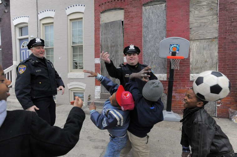 Baltimore City Police Detectives Jim Mingle, left, and Michael Boyd watch as neighborhood children (from extreme left) Trevon Halstead, 12, Cordell Jefferson, 6 (red cap), Tyrell Smith, 11 (grey cap) and Kevon Hansley, 10 (leather coat) battle over a jump ball as they pause during their patrol along Walbrook Avenue between Fulton Av. and Payson Street in the city's Western District March 20, 2013. (Karl Merton Ferron/Baltimore Sun)