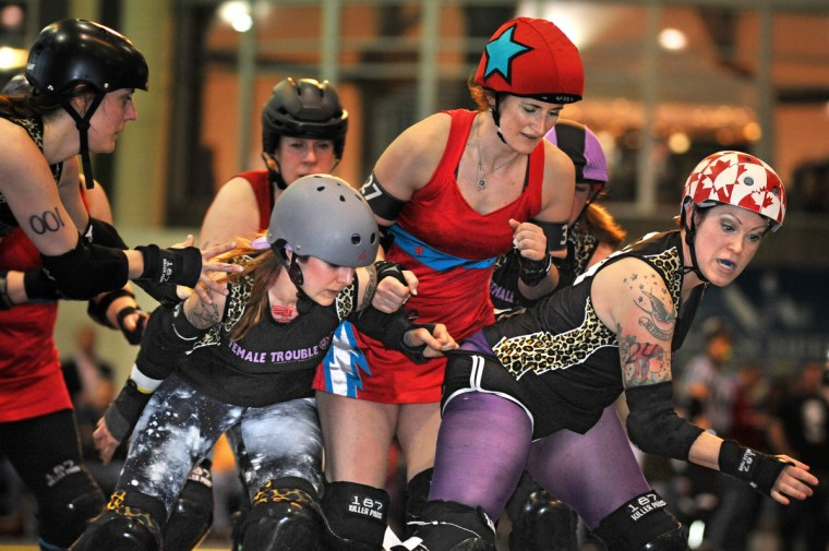 "Charm City Roller Girls' Female Trouble blockers Deathany, second from left, and Canadian Bacon, right, try to keep Philly's jammer for the Independence Dolls, Savidge Booty, from breaking through the line. Charm City Roller Girls, Baltimore's women's flat track roller derby team, held their first interleague doubleheader of the year on March 25 against their Philly rivals, at Clarence ""Du"" Burns Arena. (Amy Davis / Baltimore Sun)"