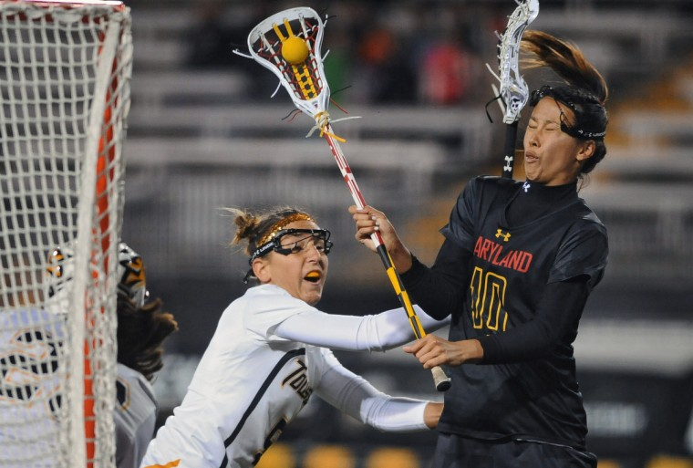 University of Maryland's Alex Aust, right, is hit on the face by Towson's Alexa Demski, left, in the second half of a lacrosse match. Maryland defeated Towson by score of 11 to 8 in college women's lacrosse on March 26, 2013. (Kenneth K. Lam/Baltimore Sun)