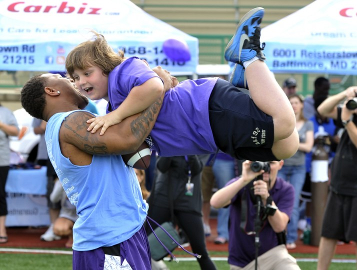 Ravens running back Ray Rice picks up Ryan Crouch, 8, Baltimore, as he plays with some of the children attending his annual football camp at the Calvert Hall Football Stadium on May 11, 2013. (Kim Hairston/Baltimore Sun)