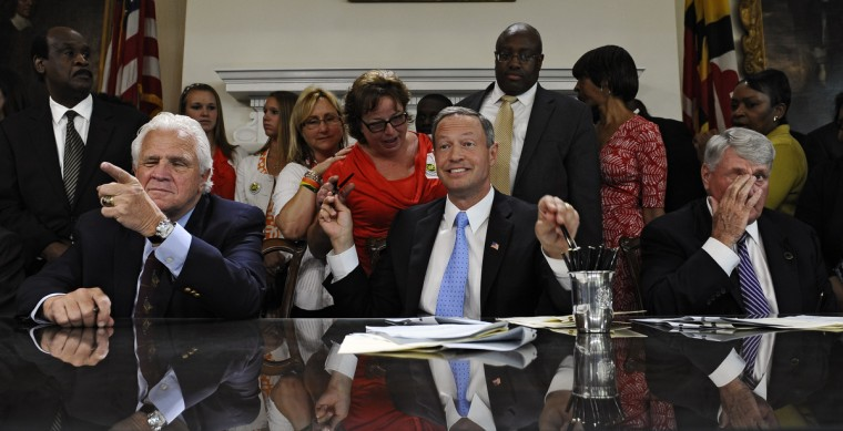 Governor Martin O'Malley, center, passes out pens while he and Senate President Thomas V. Mike Miller, left, and Speaker of the House Michael E. Busch, right, sign into law a transportation package (HB1515) that included a gas tax increase during the final bill signing ceremony of the year at the State House on May 16, 2013. (Kenneth K. Lam/Baltimore Sun)