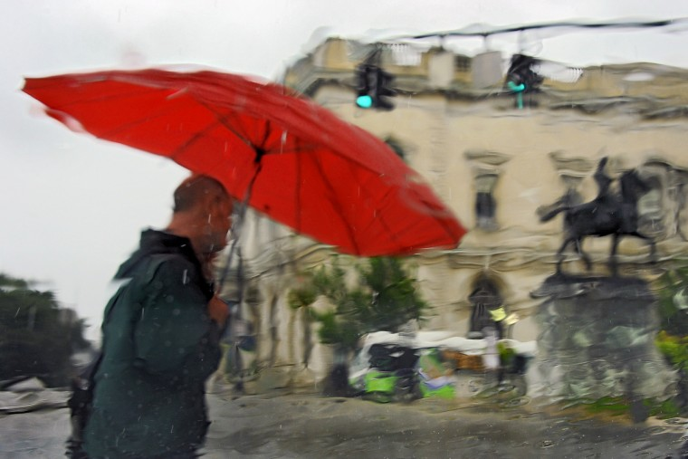 A pedestrian waits to cross Monument Street next to the Washington Monument in Mount Vernon, across from Peabody Conservatory as the scene is manipulated by water that coats a windshield on a rainy afternoon from Tropical Storm Andrea, which moves along the mid-Atlantic coast June 7, 2013. (Karl Merton Ferron/Baltimore Sun)