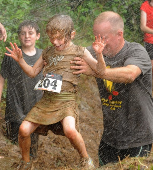 Matt Trivett helps his daughter, Amanda, escape the muddy waters. Carroll County hosts its first-ever 5k mud run through Freedom Park on June 9, 2013. (Algerina Perna/Baltimore Sun)