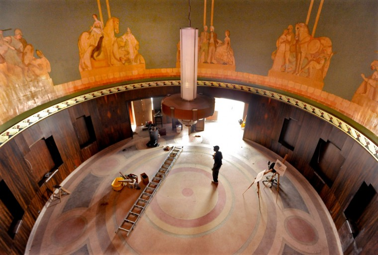 On July 31, 2013, craftsman Norman Wesson walks in the lobby of the1939 Art Deco Senator Theatre, where the murals and walnut paneling have been restored, a new Art Deco chandelier has been added, and the original terrazzo floor will be refurbished. (Amy Davis /Baltimore Sun)
