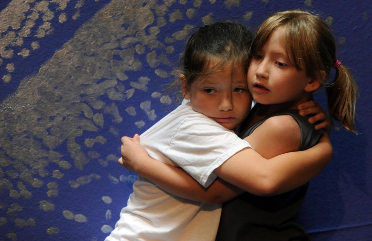 Alice Victorson, 8, left, and Nadine Victorson, 6, support each other as they watch as their sister, Catharine Victorson, 3, get a series of immunizations, August 17, 2013, before starting pre-kindergarten. (Kim Hairston/Baltimore Sun)