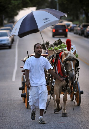 "At dusk, Arabber Yusuf Abdullah, known as ""B.J.,"" calls out the arabber holler: ""Peaches and cantaloupes, watermelon, sugar bananas and sweet grapes..."" as he walks along East Federal Street in the Berea neighborhood on August 27, 2013. (Amy Davis / Baltimore Sun)"