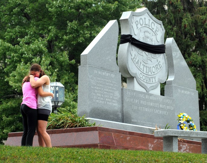 Two young women mourn at the wreath laying ceremony in front of the Police Officer monument at the Baltimore County Circuit Courthouse in honor of Police Officer First Class Jason Schneider who was killed on August 28, 2013 in Catonsville while serving a warrant. (Algerina Perna/Baltimore Sun)