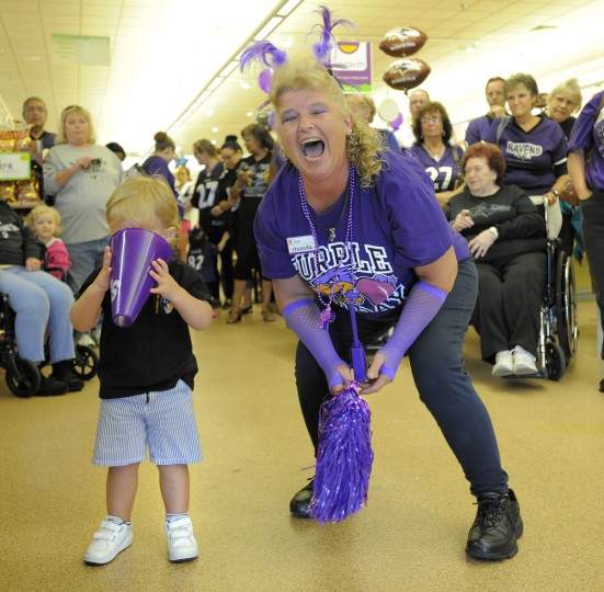 Rhonda May, right, a cashier at the Giant in Abingdon starts a few Raven cheers with the fans in the store on September 13, 2013. She handed Brayden Kinslow, 20 months-old of Bel Air, a small megaphone and he put his face in it causing her to laugh. (Lloyd Fox/Baltimore Sun)