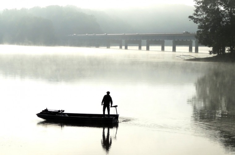 On September 20, 2013 a fisherman heads out for a day of fishing on Liberty Reservoir in the early morning fog. In the background is Route 26, Liberty Road, overpass. (Robert K. Hamilton/Baltimore Sun)
