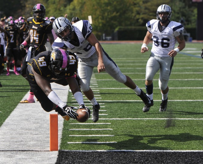 Towson's #49, Emmanuel Holder sails into the end zone to score a touchdown after being hit by #16 Joe Nick Cefalo, New Hampshire, early in the third quarter on October 5, 2013. (Kim Hairston/Baltimore Sun)