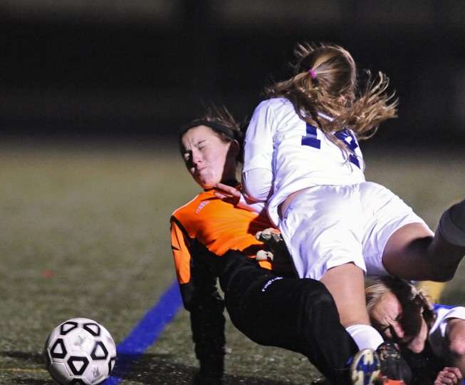 Catonsville's Deanna Eveland, right, collides with Sparrows Point goalie Madison Anthony in the first half of their Baltimore County girls soccer championship game on October 23, 2013. (Kenneth K. Lam/Baltimore Sun)