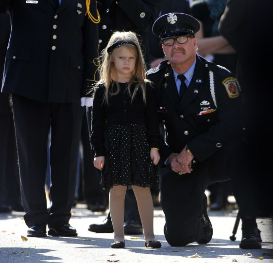 On November 2, 2013 an unidentified niece of deceased firefighter Andrew Hoffman stands next to Baltimore City firefighter/paramedic Michael Hineline as pallbearers carry her uncle's casket to a hearse outside Cathedral of Mary Our Queen. Hoffman and his girlfriend were killed by the woman's former boyfriend, a Baltimore City police officer. (Kim Hairston/Baltimore Sun)