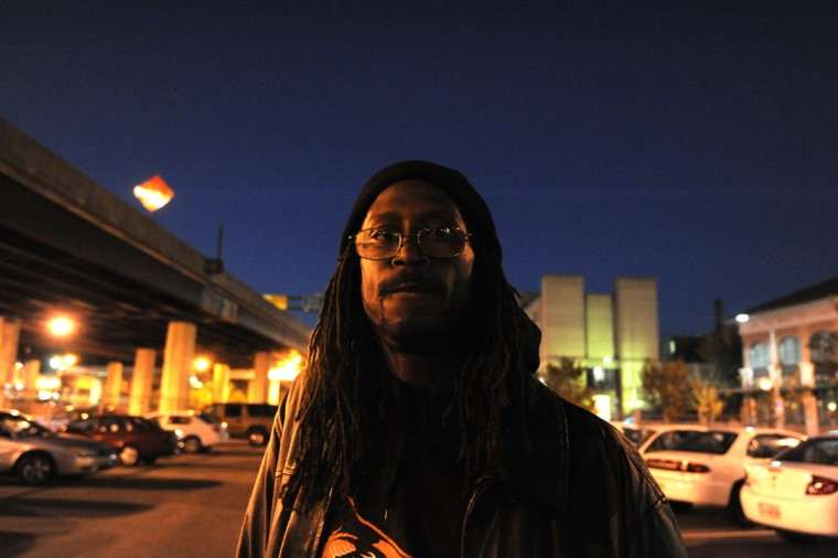 On November 13, 2013, Daymon Bittings, 48, waits for a bus in a parking lot outside the Harry and Jeanette Weinberg Housing Resource Center located in the City of Baltimore. The bus will take him to an overflow shelter. (Algerina Perna/Baltimore Sun)
