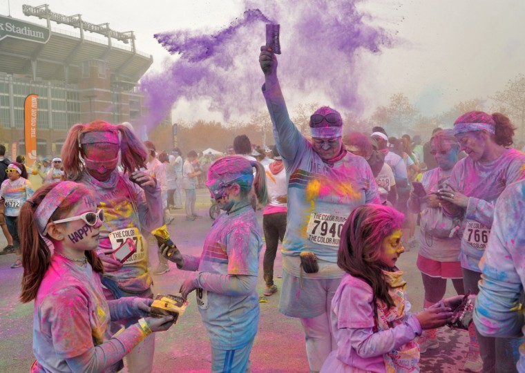 "After the morning Color Run, runners sprayed each other with packets of color powder. About 10,000 people participated in each of two 5k Color Runs on November 17, 2013, in which they were doused with colored powders along the route. BIlled as the ""Happiest 5k on the Planet."" (Amy Davis/Baltimore Sun)"