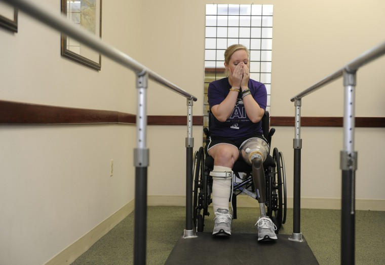 Erika Brannock, who was injured in the Boston Marathon bombing, tries her new prosthetic leg for the first time today at Dankmeyer Orthotics and Prosthetics. Here, she gets emotional as she gets ready to stand on the new leg for the first time on October 4, 2013. (Barbara Haddock Taylor/Baltimore Sun)