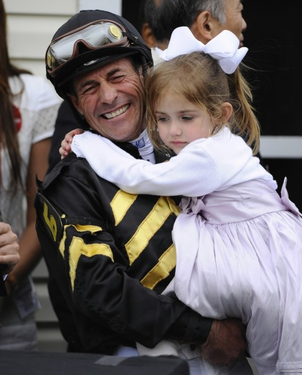 Jockey Gary Stevens, holding daughter Madison, celebrates in the winner's circle after riding Oxbow to win the 138th Preakness Stakes at Pimlico on May 18, 2013. (Kenneth K. Lam/Baltimore Sun)