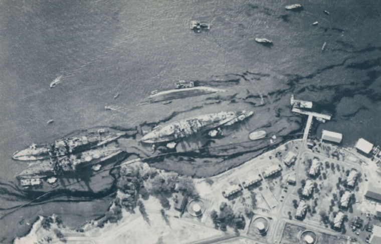 American aerial photo of ships at Pearl Harbor following the Japanese attack on Dec. 7, 1941. Left to right, USS Maryland (inboard), USS Oaklahoma (capsized), USS Tennessee (inboard), and USS West Virginia.