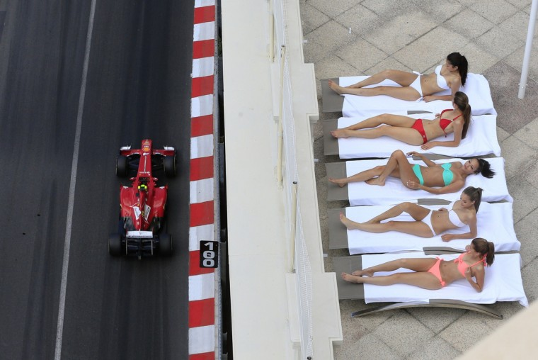Women sunbathe as Ferrari's Brazilian driver Felipe Massa drives past during the third practice session at the Circuit de Monaco in Monte Carlo on May 25, 2013 ahead of the Monaco Formula One Grand Prix. (Alexander Klein/Getty Images)