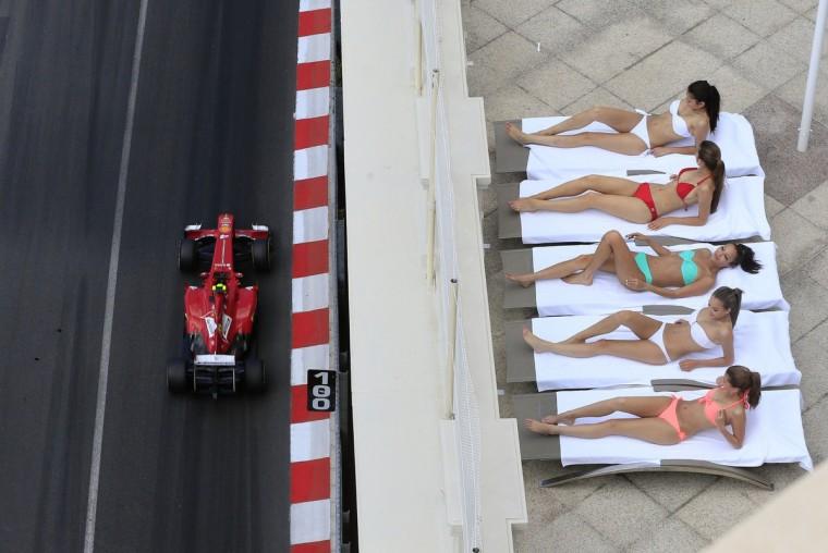 Women sunbathe as Ferrari's Brazilian driver Felipe Massa drives past during the third practice session at the Circuit de Monaco in Monte Carlo on May 25, 2013 ahead of the Monaco Formula One Grand Prix. (Alexander Klein/Getty Images)