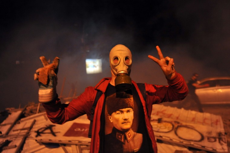 A masked protestor flashes a V-sign during the clashes near Taksim in Istanbul on June 3, 2013 during a demonstration against the demolition of the park. Turkish police on June 1 began pulling out of Istanbul's iconic Taksim Square, after a second day of violent clashes between protesters and police over a controversial development project. Thousands of demonstrators flooded the site as police lifted the barricades around the park and began withdrawing from the square. What started as an outcry against a local development project has snowballed into widespread anger against what critics say is the government's increasingly conservative and authoritarian agenda. (Ozan Kose/Getty Images)